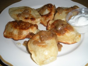 Cheddar and potato pierogies with fried onion and sour cream.